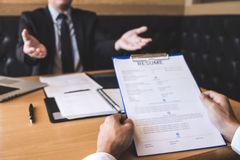 Employer or recruiter holding reading a resume during about his profile of candidate, employer in suit is conducting a job. Interview, manager resource royalty free stock image