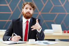 Employer talking. Confident employer talking to applicant in office Stock Photo