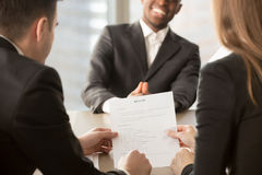Employers recruiters reviewing resume, happy applicant at backgr. Employers or recruiters review cv of black confident job applicant smiling at background during stock photography
