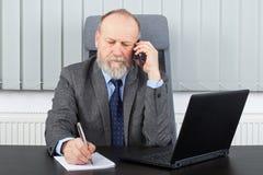 Employeur réfléchi ayant un appel téléphonique Photographie stock