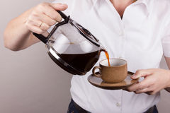 Employing coffee in a cup. Employing coffee in the cup by a woman Stock Photography