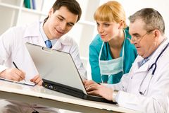 Employment. Three specialists looking at laptop screen while elderly man typing document Stock Images