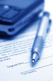 Employment agreement. Close-up of silver pen and mobile phone on employment agreement. Selective focus on top of pen. Toned monochrome image Royalty Free Stock Photography