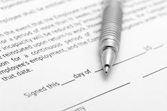Employment agreement. Close-up of silver pen on employment agreement. Selective focus on top of pen Royalty Free Stock Photos
