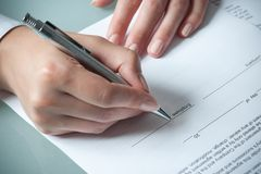 Employment agreement. Female hands filling out employment agreement contract Stock Photo
