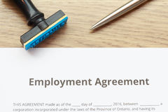 Employment Agreement document lay down on wooden desk with rubbe. R stamp and pen Royalty Free Stock Image
