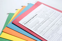 Employment Application Form. With colored folders in background Royalty Free Stock Images