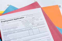 Employment Application Form. With colored folders in background Royalty Free Stock Photo