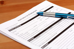 Employment Application Form. And blue pen on table Stock Image