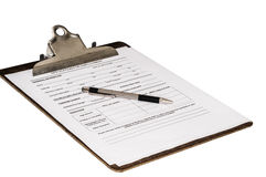Employment Application. Job application on a clipboard with a pen laying on top. Waiting to be filled out by a propective employee. Isolated on a white Royalty Free Stock Images