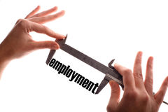 Less employment. Color horizontal shot of two hands holding a caliper and measuring the word employment Royalty Free Stock Photography