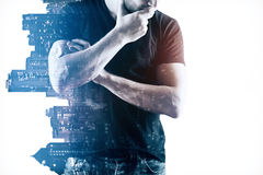 Employment concept. Thoughtful young man in casual shirt on abstract night city background. Employment concept. Double exposure stock photo