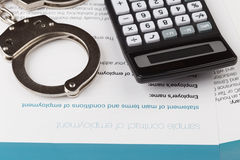 Employment contract. With handcuffs and calculator Royalty Free Stock Photo