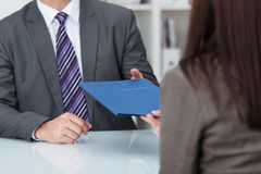 Employment interview. With a close up view of a female applicant handing over a file containing her curriculum vitae to the businessman conducting the interview