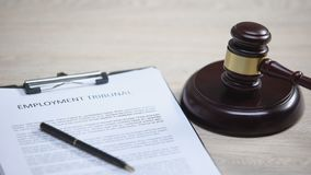 Employment tribunal document on table, gavel striking on sound block, dispute