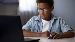 Empollón afroamericano que juega a los juegos de ordenador en vez del aprendizaje, apego del niño fotos de archivo libres de regalías