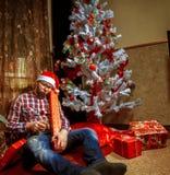 Empollón borracho en el sombrero de santa que miente debajo del árbol de Christma con mucho Fotografía de archivo libre de regalías