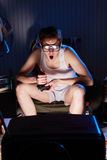Empollón del videojugador que juega a los videojuegos en la televisión Foto de archivo