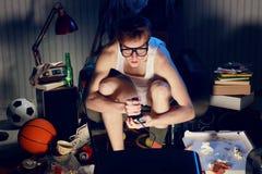Empollón del videojugador que juega a los videojuegos en la televisión Fotografía de archivo libre de regalías