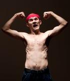 Empollón divertido que muestra su bíceps Foto de archivo
