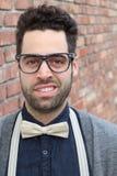 Empollón Guy With Glasses, corbata de lazo, y fondo de la pared de ladrillo imagen de archivo libre de regalías