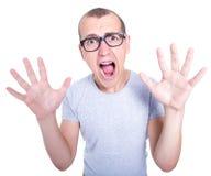 Empollón - hombre joven divertido en vidrios con los apoyos en los dientes que grita Imagen de archivo libre de regalías