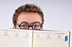 Empollón joven que oculta detrás de agenda Fotos de archivo libres de regalías