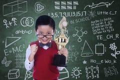Empollón lindo que sostiene el trofeo en clase Fotos de archivo