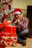Empollón solo triste con un manojo de regalos de la Navidad Imágenes de archivo libres de regalías