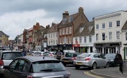 Emporkommende englische Marktstadt, die altmodische Shops und einen verstopften Parkplatz zeigt lizenzfreie stockfotografie