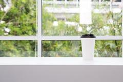 Emportez la tasse de café placée sur le rebord de fenêtre blanc Le fond est un train dans la capitale image stock