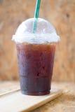 Emportez la tasse en plastique d'americano glacé de café noir dans un café Image libre de droits