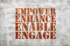 Empower, enhance, enable, engage graffiti. Empower, engage, enable, and enhance inspirational leadership concept - graffiti sign on stucco wall Royalty Free Stock Image