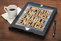 Empower, enhance, enable and engage. Motivational business concept - a collage of words in letterpress wood type on a digital tablet Royalty Free Stock Image