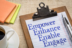 Empower, enhance, enable and engage. Motivational leadership, coaching or business concept - empower, enhance, enable and engage  words on a clipboard with a cup Stock Photography