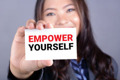 EMPOWER YOURSELF message on the card shown by a businesswoman Stock Photos