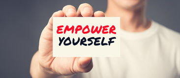 EMPOWER YOURSELF, message on the card shown by a man Stock Image