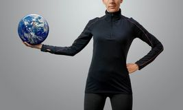 Empowered fit woman holding world in her outstretched hand. Against a gray background stock image