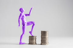 Empowered women stepping up the income ladder concept. Purple fe. Male figurine clilmbing up on piles of coins. Isolated on white with copy space Stock Image