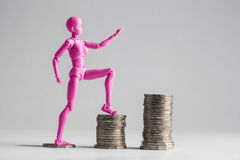 Empowered women stepping up the income ladder concept. Purple fe. Empowered women stepping up the income ladder concept. Pink female figurine clilmbing up on Royalty Free Stock Images