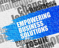 Empowering Business Solutions on White Wall. Business Education Concept: Empowering Business Solutions. Blue Inscription on White Brick Wall. Empowering Stock Photos