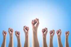 Empowering women power, human rights and labor day concept with strong fist hands  on blue sky