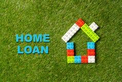 Empréstimo hipotecário colorido da casa e do tex de blocos do brinquedo escrito na grama no investimento da operação bancária e d foto de stock royalty free