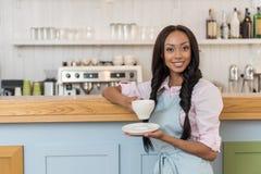 Empregada de mesa afro-americano no café bebendo do avental e vista da câmera no café fotos de stock royalty free
