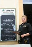 Empregada de mesa, Alemanha, estando pela placa do menu Foto de Stock