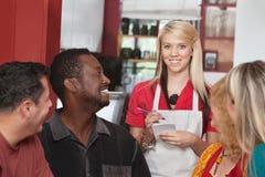 Empregada de mesa com clientes diversos imagens de stock