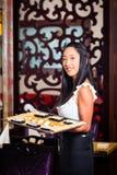 Empregada de mesa com o sushi no restaurante Fotografia de Stock Royalty Free