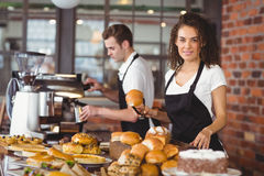 Empregada de mesa de sorriso que guarda o rolo de pão com tong foto de stock royalty free