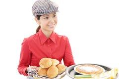 Empregada de mesa de sorriso que leva uma refeição Imagem de Stock