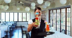 Empregada de mesa de sorriso que oferece uma bebida do cocktail video estoque